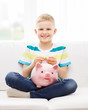 smiling little boy with piggy bank and money