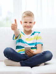 smiling boy with smartphone showing thumbs up