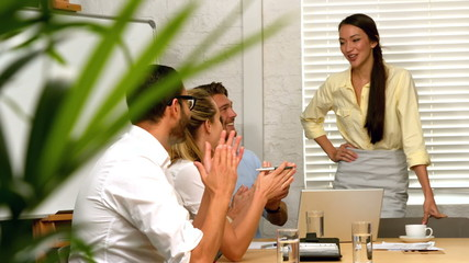 Casual business team having a meeting and applauding colleague