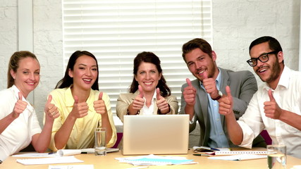 Casual business team showing thumbs up to camera during meeting