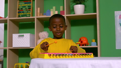 Cute little boy playing xylophone in classroom