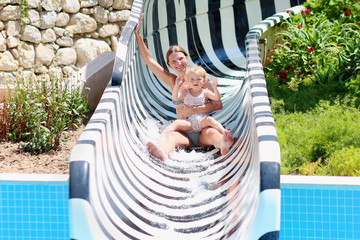 Mother and daughter having fun on slide in aqua park