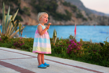 Little girl eating ice cream walking on beautiful promenade