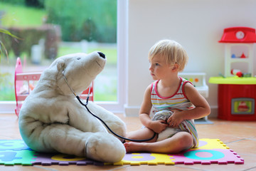 Little girl plays doctor providing healthcare to teddy bear