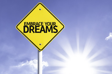 Embrace your Dreams road sign with sun background
