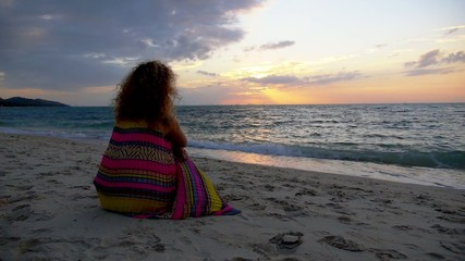 Worried Sad Girl Sitting on the Beach at Sunset. Slow Motion.