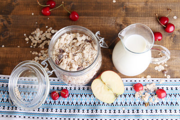 Homemade granola in glass jar, fresh cherries and jug with milk