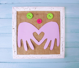 Wooden frame with paper arms and colorful buttons