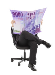 Business man sitting on a chair with taiwan currency in hands