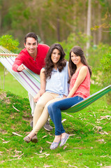 two beautiful girls and a young man in hammock outdoors