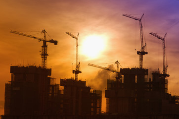 Industrial landscape with silhouettes of cranes on the sunrise b