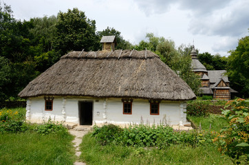White traditional Ukrainian rural wooden house with hay roof