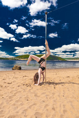 girl make pole dance in a swimsuit on the beach background sky