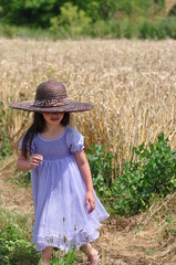 Little girl with hay hat on the golden wheat field
