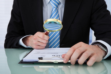 Businessman Examining Invoice Through Magnifying Glass