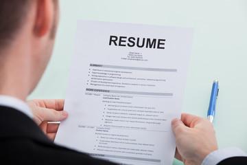 Businessman Reading Resume At Office Desk