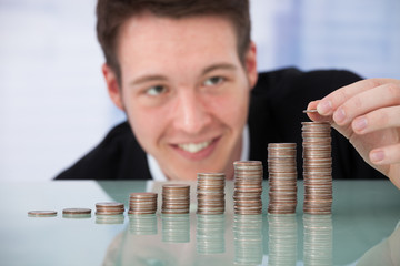 Happy Businessman Stacking Coins In Increasing Order