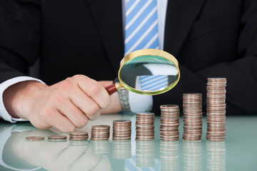 Businessman Examining Coins Stacked As Bar Graph