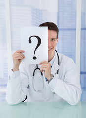 Doctor Holding Paper With Question Mark At Desk