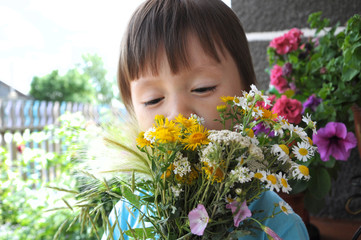 Boy smelling summer bouquet of wildflowers