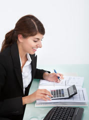 Businesswoman Calculating Bills At Desk