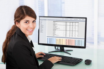 Confident Businesswoman Using Computer At Desk
