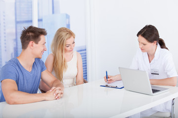 Doctor Discussing Report With Young Couple In Clinic