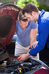 Car Owner With Mechanic Testing Car Battery