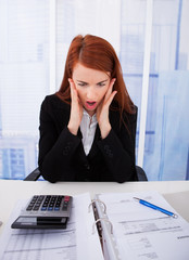 Shocked Businesswoman Looking At Tax Papers