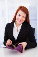 Happy Businesswoman Putting Dollar Bills In Wallet