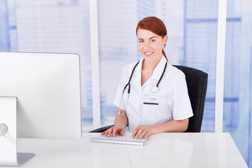 Confident Female Doctor Using Computer