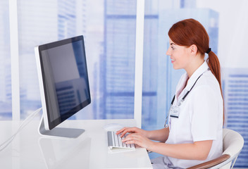 Female Doctor Using Computer At Desk In Clinic