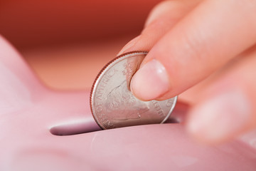 Hand Inserting Coin In Piggybank