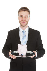 Businessman With Piggybank On Tray