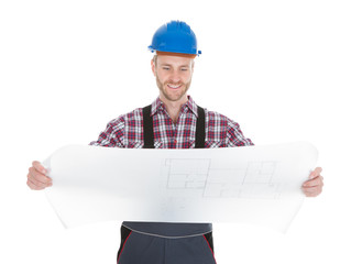 Worker Reading Blueprint Over White Background
