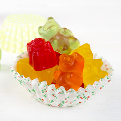 colorful jelly bears on light wooden background