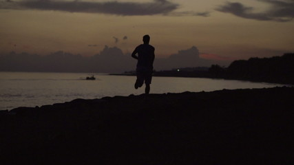Alone man jog on the beach at night, steadycam shot, slow motion