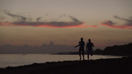 Couple jogging on the beach, steadycam shot, slow motion shot