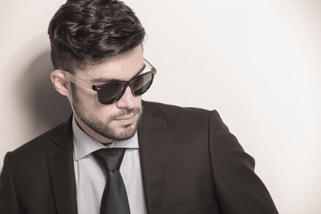 sexy young business man wearing sunglasses looks away