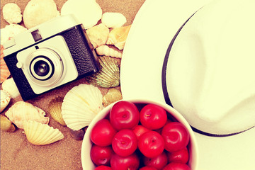 Red plums, old camera, shells and white hat on sand vintage