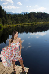 Young Woman In Colorful Dress At The Lake Watching a Dragonfly