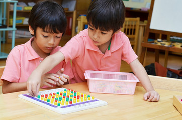 Little boys study color of pin made of montessori educational ma