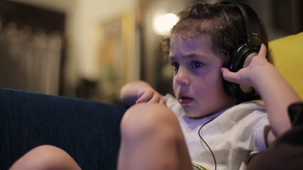 Boy watching tv and wearing headphones, closeup