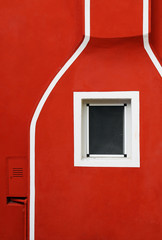 Detail of a red facade with white lines and a small window
