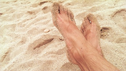 Male feet and sand on the sunny beach
