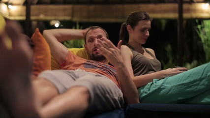 Unhappy couple having disagreement at night in room