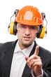 Businessman in safety hardhat helmet gesturing exclamation point