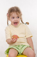 The three-year girl laughing eating a bun