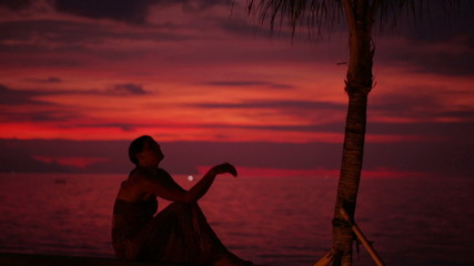 Woman sitting alone in the darkness at seashore, steadycam shot