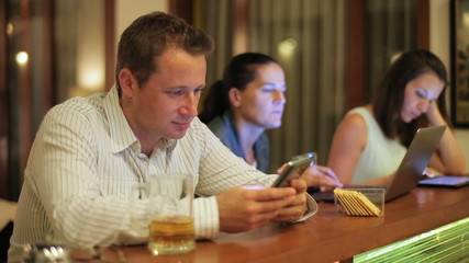 Man using cellphone in pub at night and woman working on technol